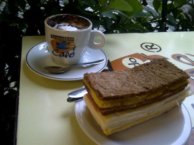 Capuccino com leite magro e sanduiche de pao de miga preto ou tradicional de queijo com presunto.